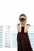 Girl looking through binoculars, standing on pier
