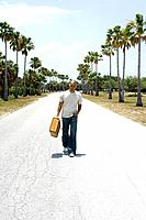 Man walking down center of road, carrying suitcase, listening to headphones