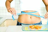 Woman wrapping a measuring tape around her stomach, plate of vegetables on table