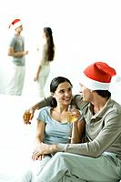 Couple sitting on sofa, drinking champagne, man wearing Santa hat (thumbnail)