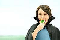Boy wearing vampire cape, eating large lollipop, portrait