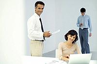Professionals in office, man standing and holding document, woman sitting in front of laptop computer