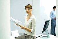 Woman sitting in office, holding documents, smiling at camera
