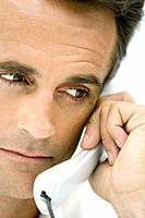 Man using landline phone, looking away, cropped