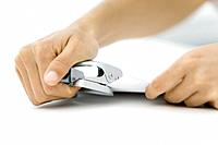 Person using hole puncher on document