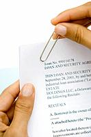 Woman putting paper clip on loan contract, cropped view, close-up
