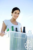 Woman carrying recycling bin filled with glass bottles, smiling at camera