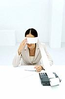 Woman sitting at desk, tape from an adding machine wrapped around her eyes, touching face