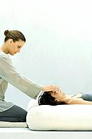 Woman receiving reiki head massage