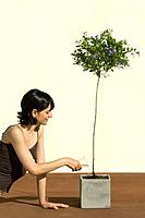 Woman watering potted plant, smiling (thumbnail)