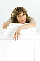 Woman leaning over stack of towels on counter, looking at camera