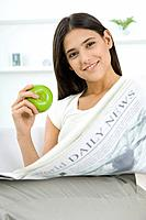 Female sitting, holding apple and newspaper, smiling at camera