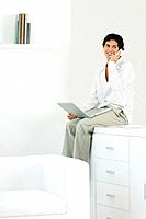 Man sitting on counter, talking on landline phone, holding laptop on lap