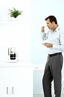 Man standing by coffee maker, taking a sip of coffee, holding saucer