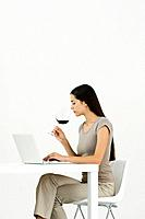 Woman using laptop at table, holding glass of wine (thumbnail)