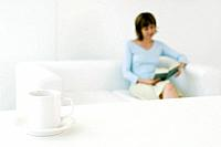Woman reading book on sofa, focus on coffee cup in foreground