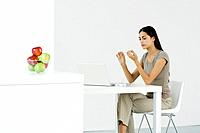 Woman sitting at table in front of laptop computer, filing nails (thumbnail)