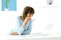 Woman looking at laptop computer, drinking coffee