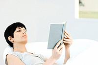 Woman reclining in chair, reading book