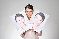 A woman holding photographs of herself