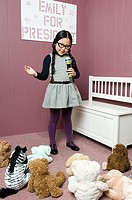 A girl giving a speech to her toys