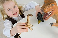 A girl playing with toy dinosaurs