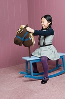 A girl sat on a rocking horse