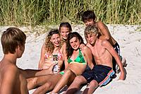 Teenage boy 14-16 taking photograph of friends on beach with mobile phone, smiling