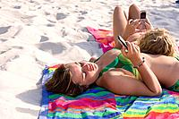 Teenage girls with mobile phones sunbathing on beach, one with head on friend (thumbnail)