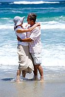 Mature couple embracing in shallows on beach