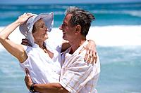 Mature couple embracing on beach, woman holding hat on head, smiling