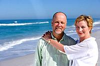 Mature couple on beach, woman with arms around man, smiling, portrait