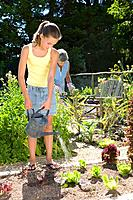 Girl 10-12 gardening with grandmother