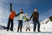 A family jumping at a ski resort