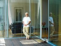 Senior man by glass doors on decking, smiling, portrait