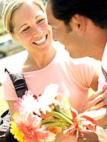Man giving woman bunch of flowers, woman smiling at man, close-up