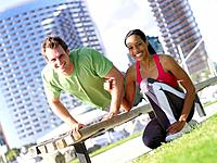 Woman by man exercising on bench outdoors, smiling, portrait