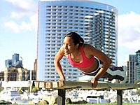 Young woman doing pushups on bench outdoors, low angle view
