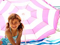 Girl 3-5 in swimsuit on beach by parasol, smiling, portrait