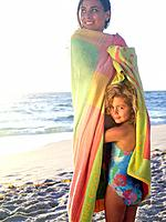 Mother and daughter 5-7 wrapped in towel on beach, smiling, portrait of girl
