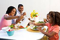 Family of four at dinner table, mother pouring water for daughter 7-9