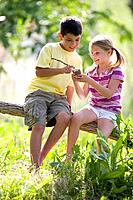 Boy 9-11 showing girl 8-10 MP3 player outdoors, smiling