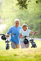 Mature couple walking with bicycles outdoors, smiling