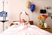 Girl 5-7 reading card in hospital bed