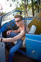 Bare chested man in convertible car, smiling, portrait