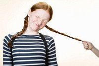 A girl having her pigtail pulled