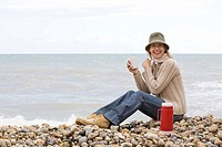 Woman having a drink at the beach