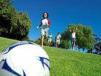 Family of four playing football outdoors, low angle view