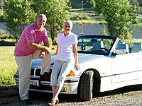 Couple on bonnet of convertible car, portrait