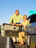 Mature couple getting out of car on roadside, portrait